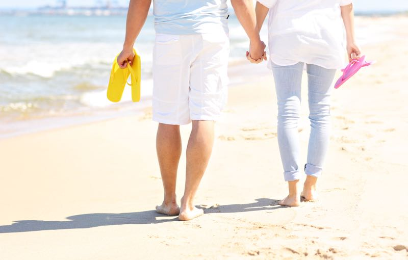 Couple living the simple life getting a little exercise in a very pleasant manner walking along a warm sandy beach