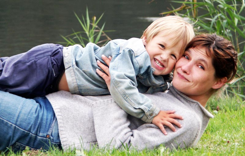 Mother and young son enjoying the simple life beside a peaceful river
