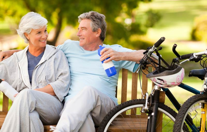 Older couple enjoying a break in the park after cycling